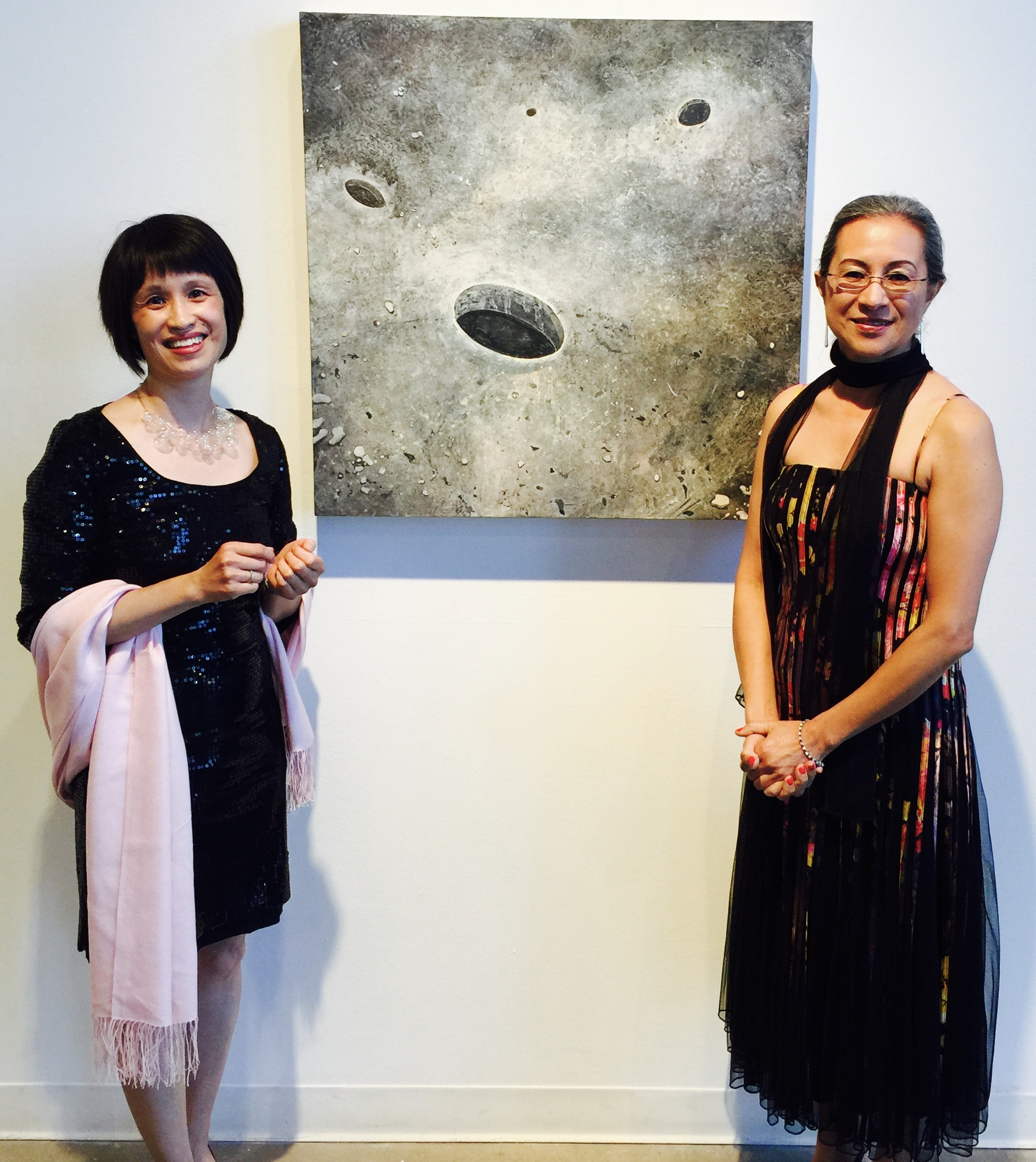 Jing Yeng Lim and Dolores Arce-Kaptain admiring Visual Arts faculty member Lanny DeVuono's painting